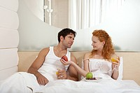 Couple eating fruits in bed