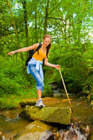 Young woman hiking through the woods and trying to cross a stream