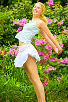 Sporty young girl enjoying the beautiful day and jumping up in the air in the garden