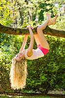 Young woman having fun in the garden and hanging on to a tree