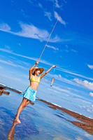 Young woman holding her just caught fish high up in the air