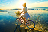 Young woman wearing a white dress riding her bike on the beach at sunset