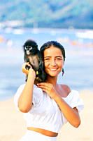 Portrait of a smiling girl with a monkey on her shoulder