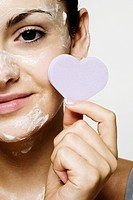 Young woman with cosmetic and cleansing foam on her face.