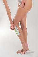 Low section view of a woman shaving her leg with a razor