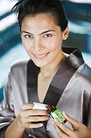 Woman holding a bottle of aromatherapy oil and smiling