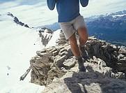 Hiker walking along mountain ridgecrest high above valley Canada Alberta Banff National Park