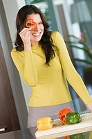 Woman looking through a slice of red bell pepper