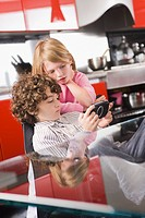 Boy playing a video game and his sister standing beside him
