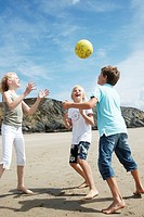 Two boys and a girl playing ball on the beach, Bretagne, France, Europe