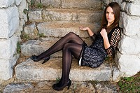 Fancy young woman is sitting on outdoor staircase