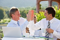 Happy businessmen giving high five and drinking coffee at cafŽ