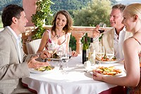 Well_dressed couples dining at table on restaurant balcony