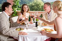 Well_dressed couples toasting wine glasses at table on restaurant balcony