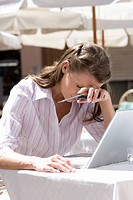 Frustrated businesswoman holding cell phone with head in hands at sunny, outdoor cafŽ