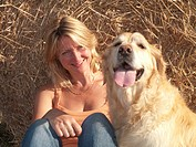 Smiling woman with dog leaning against hay bale