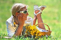 blonde young woman lying in a spring meadow, basket with flowers beside her.