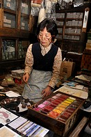 Sales clerk kneeling on a tatami mat and showing different mineral colours for Nihonga painting in a traditional shop for art supplies, Kyoto, Japan, ...