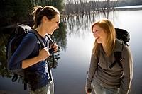 Two women laughing beside lake