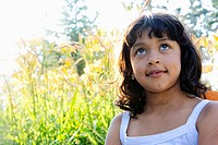 10 year old Hispanic girl looking up to sky, day dreaming in a garden of day lilies.