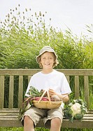 Boy on bench with vegetables