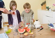 boy and girl preparing fruit smoothies