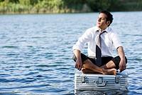 businessman sitting on floating suitcase