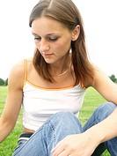 brunette woman sitting on lawn