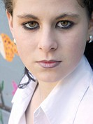 portrait of a young darkhaired woman in white blouse, looking serious, Germany