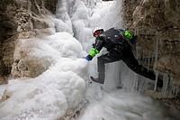 Ice climber on a frozen waterfall in the Kalkalpen National Park, Upper Austria