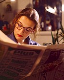 young woman with glasses reading newspaper, Germany
