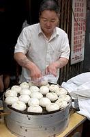 Man making traditional Beijing dumplings on a Beijing street