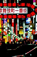 Neon signs over busy street at night