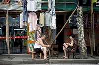 A woman and a man sitting outside his home with his clothes on the street. Shanghai, China