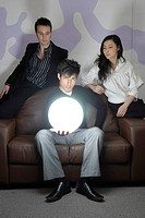 A young business man holding a brightly glowing globe with his colleagues looking