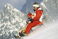 mother with child on a taboggan, Austria, Alps