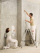 Couple measuring and painting wall in living room