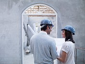 Couple holding blueprints in house under construction