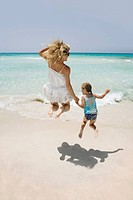 Mother and daughter jumping on beach