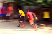 young men playing soccer in the street