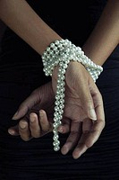 Woman´s hands tied up with pearl necklace