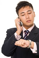 A young asian businessman looks at his watch whilst on the phone