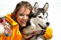 young woman in yellow ski suit with huskey in snow