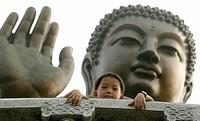 Boy in front of a bronze Buddha at Po Lin Monastery, Lantau Island, fishing village, Hong Kong, China, Asia