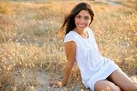 Beautiful indian brunette having a rest on a golden summer field
