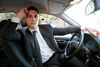 Young suit businessman posing inside his car
