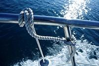 Nautical marine fender knot around stainless steel lee on blue ocean sea