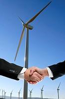 Businessmen handshake environmental agreement over wind mills