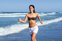 Beautiful summer indian brunette girl jumping on the blue beach