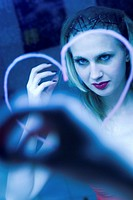 young blond sexy woman dressing her hair in front of a mirror, a violet heart is painted on